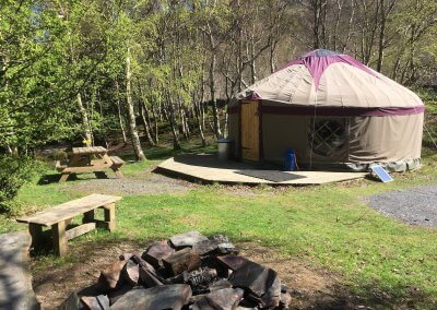 Large yurt has outdoor camp fire and seating
