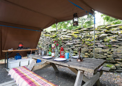 Outdoor kitchen shelter lit with solar lights and lanterns